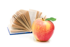 Open book and an apple on a white background Stock Photos