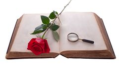 Open book with rose and magnifying glass. Isolated Stock Images