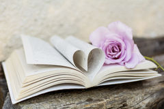 Open book with rose on a wooden background Stock Photography