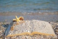 Open book sand seashells sea star beach sea shore blue sky white wave summer weekend vacation Royalty Free Stock Photo