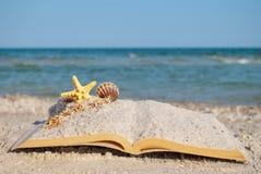 Open book sand seashells sea star beach sea shore blue sky white wave summer weekend vacation Stock Image
