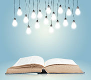 Open book with shining lamps Royalty Free Stock Image