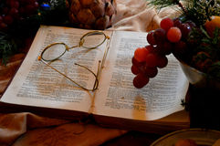 Open Book Spectacles. An open book with a pair of spectacles on the book and some grapes hanging out over a bowl next to the book royalty free stock image