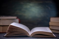 Open book on a stack of books on a table on a dark background. Education and reading of paper books stock images