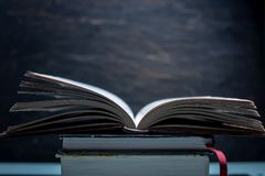 Open book on a stack of books on a table on a dark background. Exam preparation in schools and colleges stock photo