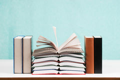 Open book, stack of hardback books on table. Back to school. Copy space Stock Image