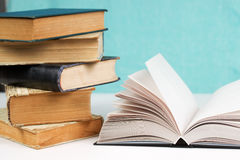 Open book, stack of hardback books on table. Back to school. Copy space stock images
