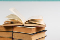 Open book, stack of hardback books on table. Back to school. Copy space Stock Photography