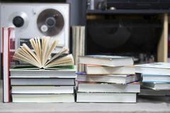 Open book, stack of hardback books on table. Top view. Royalty Free Stock Photo