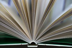 Open book, stack of hardback books on table. Top view. Stock Photo