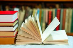 Open book, stack of hardback books on table. Top view. Royalty Free Stock Images