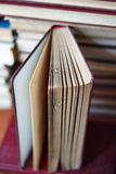 Open book, stack of hardback books. On wooden table royalty free stock photo