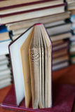 Open book, stack of hardback books. On wooden table royalty free stock photography