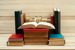 Open book, stack of hardback books on wooden table.  Back to school. Copy space.  stock photography