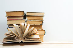 Open book, stack of hardback books on wooden table. Back to school. Copy space.  Royalty Free Stock Images