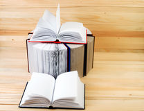 Open book, stack of hardback books on wooden table. Back to school. Copy space.  Stock Image