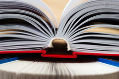 Open book, stack of hardback books on wooden table. Back to school. Copy space Royalty Free Stock Photo