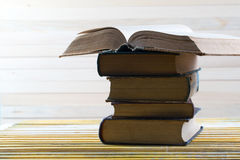 Open book, stack of hardback books on wooden table. Stock Photography