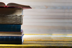 Open book, stack of hardback books on wooden table. Royalty Free Stock Image