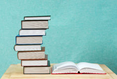 Open book, stack of hardback books on wooden table. Stock Photos