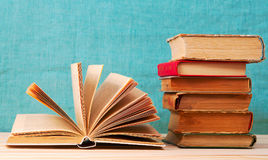 Open book, stack of hardback books on wooden table. Royalty Free Stock Photos