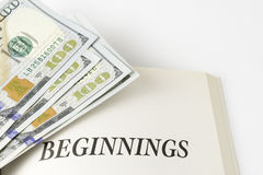 Open Book With Stack Of Hundred Dollars Bills. Beginnings written on page, done on white background Stock Photo