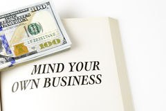 Open Book With Stack Of Hundred Dollars Bills. Mind your own business written on book, done on white background Royalty Free Stock Image