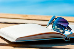 Open book and sunglasses on the background of the sea Stock Photos