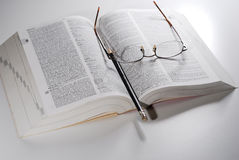 Open book on a table. Open book, reading glasses with pencil on a table Stock Image