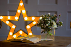 The open book on a table against the background of a star. Nearby flowers Royalty Free Stock Photos