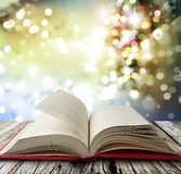 Open book. On table in front of bright lights Royalty Free Stock Photography