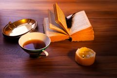 An open book on the table. A gloomy burning candle. royalty free stock photo