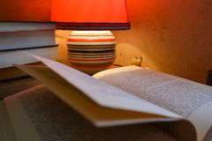 Open book and a table lamp. Open book on the table. A stack of books and a table lamp. Red table lamp, candle and paper books royalty free stock photography