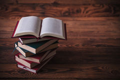 Open book on top of pile of books. With book sign in the middle , on old wood background, studio picture Royalty Free Stock Images