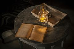 Open book under the lamp with a candle stock photos