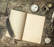 Open book and vintage office supplies feather pen, inkwell Royalty Free Stock Photos