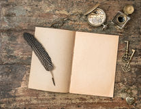Open book and vintage writing accessories. Textured wooden backg Royalty Free Stock Photography