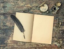Open book and vintage writing accessories. Wooden texture backgr Royalty Free Stock Images