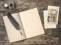 Open book, vintage writing tools feather pen and inkwell Stock Photo