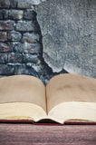 Open book on wall background Stock Photo