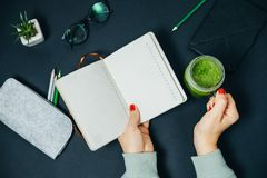 Open book in woman hands and Jar with fresh green smoothies at o Royalty Free Stock Photography