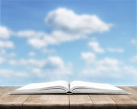 Open book is on wood planks over cloudy sky background Royalty Free Stock Images