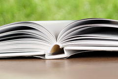Open book on a wood table  over green  light background Royalty Free Stock Photos