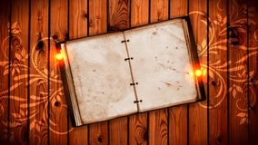 Open book on wooden background with lights and ornaments. Royalty Free Stock Photo