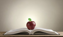 Open book on a wooden Desk with a red Apple Stock Image