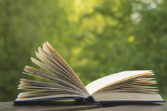 Open book. On a wooden garden table, green nature background Stock Image
