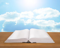 Open book on wooden plank bright sky background Stock Images