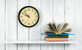 The open book on a wooden shelf and watches. Royalty Free Stock Photo