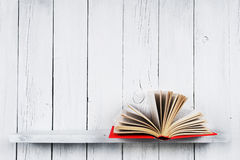 The open book on a wooden shelf. Royalty Free Stock Photo