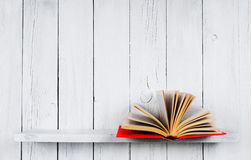 The open book on a wooden shelf. A wooden, white background royalty free stock photos